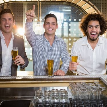 Friends raising their fist while having beer at bar counter in bar